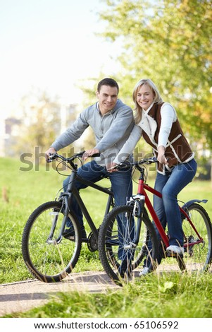 The happy couple on bicycles in the park - stock photo