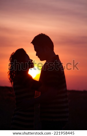 The happy couple on the background of the sunset