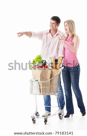 The happy couple with a cart with food on a white background - stock photo