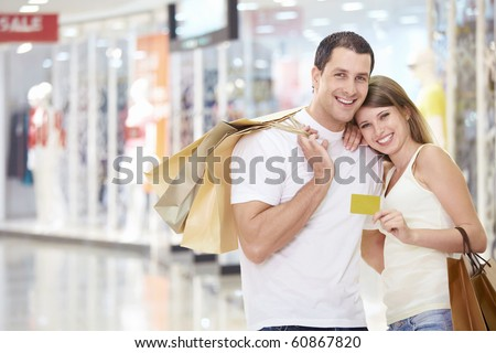 The happy couple with a credit card and shopping at the store