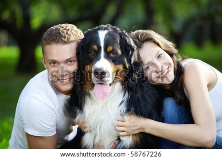The happy couple with a dog in the park - stock photo