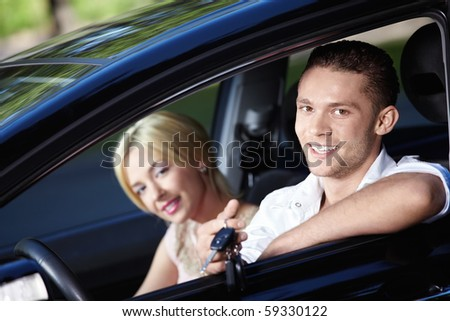 The happy couple with the keys in the car - stock photo