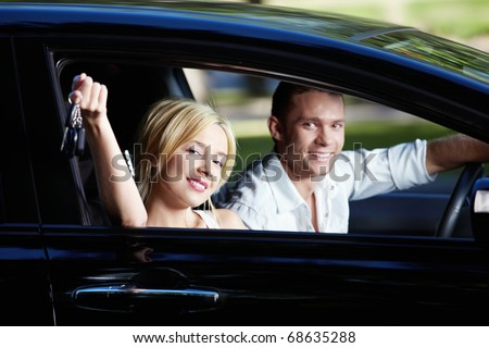 The happy couple with the keys in the car