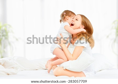 The happy family mother and baby daughter playing and laughing baby kissing in bed - stock photo