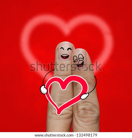 the happy finger couple in love with painted smiley and hold heart - stock photo