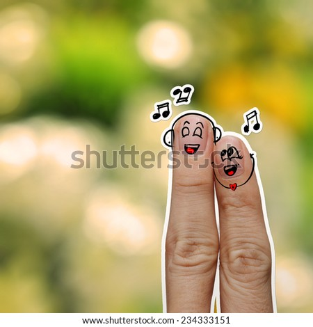 the happy finger couple in love with painted smiley and sing a song on flower nature background  - stock photo