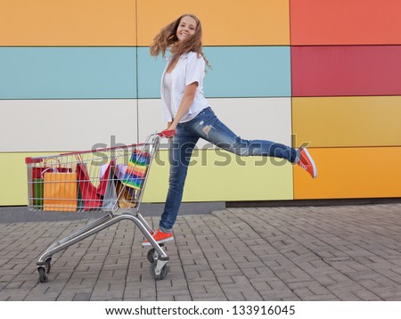 The happy girl the teenager joyfully jumps near to the cart full of purchases - stock photo
