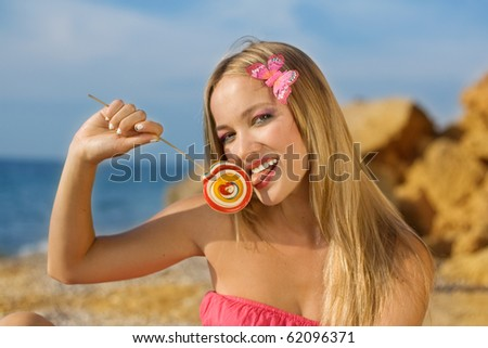 The happy girl with a bright sugar candy - stock photo