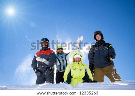 The happy group of people throws a snow on a background of the blue sky - stock photo