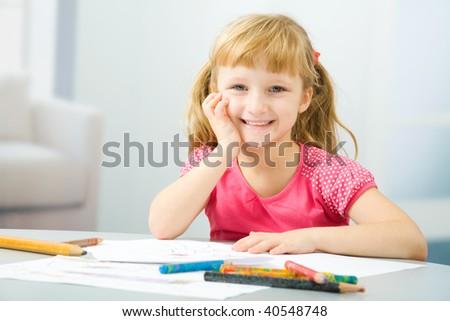 The happy little girl draws - stock photo