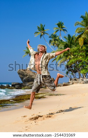 The happy man is jumping on the beach - stock photo