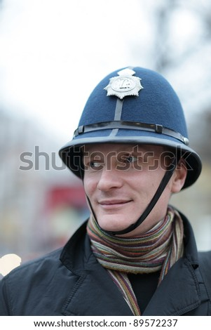 The happy man posing in british police hat - stock photo
