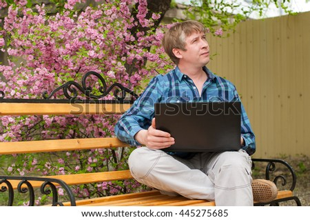 The Happy man sitting on bench and using laptop in a park