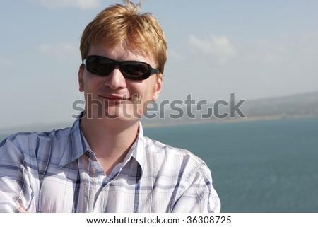 The happy tourist poses on Sevan background, Armenia - stock photo