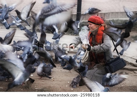 The happy woman feed the birds