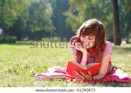 the happy woman lays on a grass and reads the book - stock photo