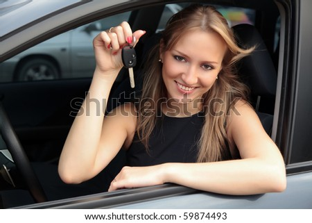 The happy woman showing the key of her new car - stock photo