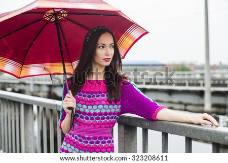 The happy woman walks on the bridge with an umbrella in a pink dress