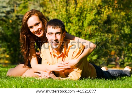 The happy young couple embraces on a grass