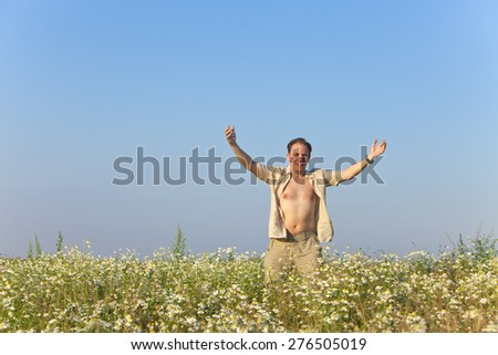 The happy young man  in the field of camomiles