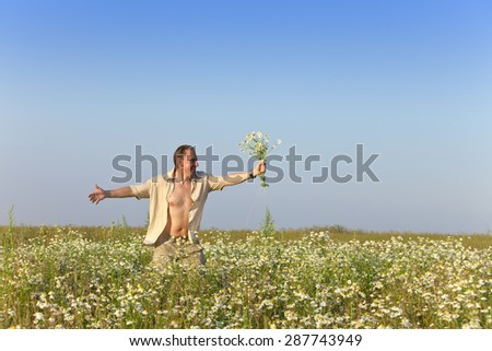 The happy young man in the field with a bouquet of camomiles - stock photo