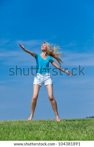 The happy young woman jumps in the field