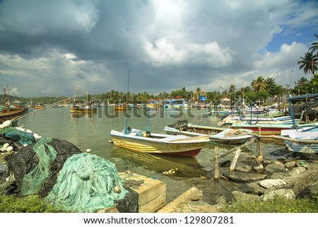 The harbor of Mirissa on the tropical island of Sri Lanka with dark and gloomy and sinister clouds, warning for a thunder and lightening storm - stock photo