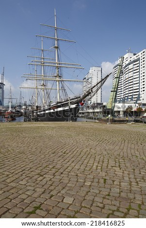 The harbour basin with historical ships and residental towers at the inner city of Bremerhaven (Germany, federal state Bremen) taken at a sunny afternoon. This image is retouched. - stock photo