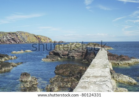 the harbour wall and cliffs at St. Abbs in Berwickshire - stock photo