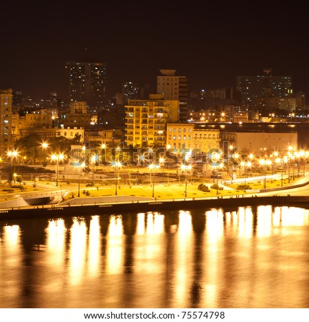 The Havana skyline featuring modern buildings , the malecon and the entrance to the bay illuminated at night with reflections on the water