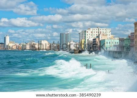 The Havana skyline with big sea waves crashing on the Malecon seawall - stock photo