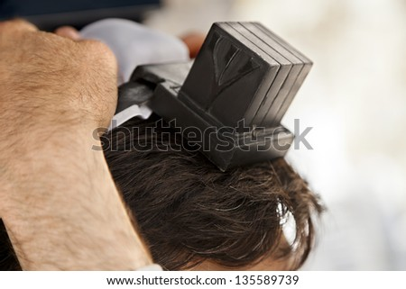 The head of an adult Caucasian man is being wrapped in a leather strap, part of the Jewish phylacteries (Teffilin, Tefilin, Tfilin) wearing ceremony and prayer. - stock photo