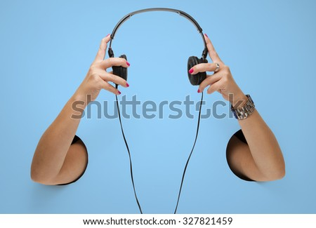 The headphones in a female hands through the holes - stock photo