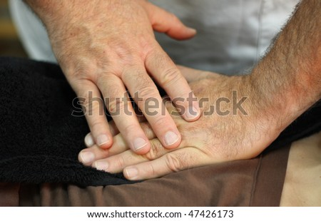 The healing hands of an osteopath - stock photo