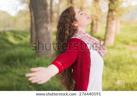 The healing power of nature. Beautiful young woman taking a deep breath, enjoying the freshness of nature, posing with her arms outstretched. - stock photo