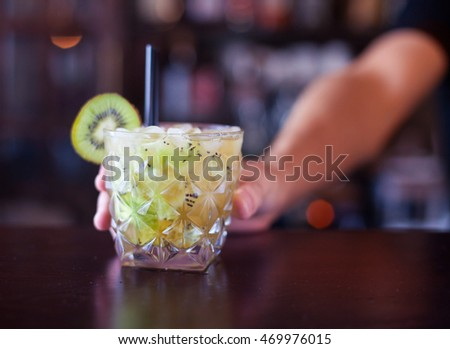 the healthy green cocktail decorated with a slice of a kiwi on a bar counter, close up