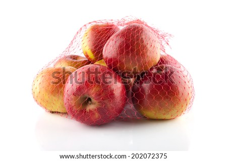 The heap of apples packaged in the red net - stock photo