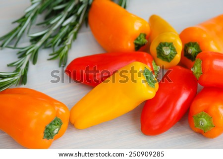 The heap of fresh mini peppers with rozmarin - stock photo