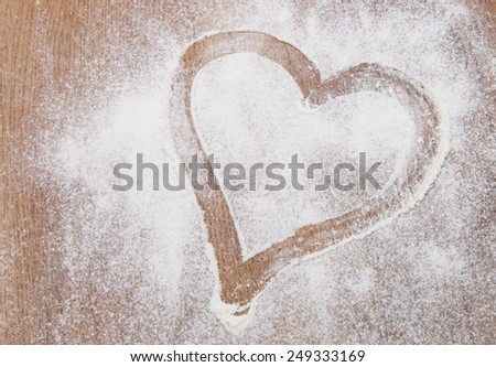 The heart of the flour on the table from the old boards. - stock photo