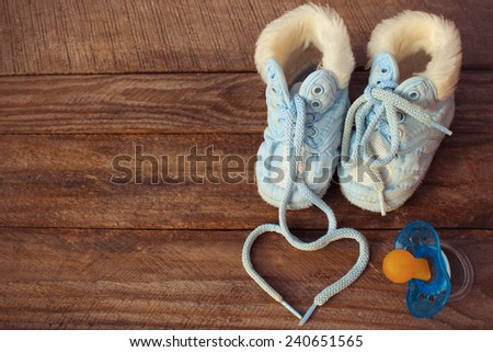 The heart symbol is drawn laces of children's shoes and a pacifier on the old wooden background. Toned image  - stock photo