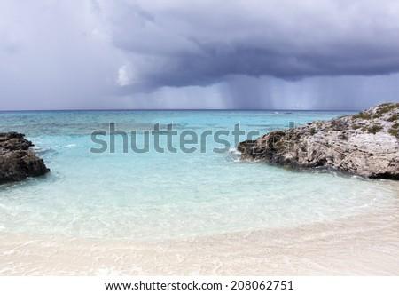 The heavy rain is coming towards Half Moon Cay (The Bahamas). - stock photo
