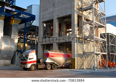 The heavy truck is loading the concrete powder to the packing factory - stock photo