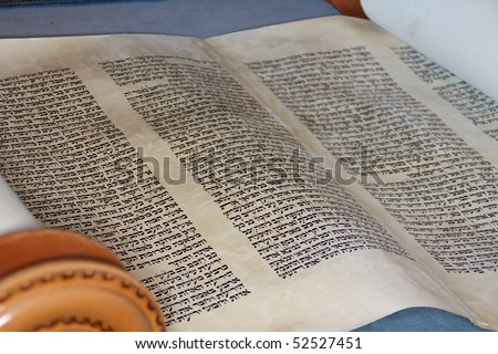 The hebrew Torah, displayed here on a synagogue alter, is hand written on goat skin parchment by a specially trained scribe using a feather quill - stock photo