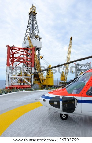 The helicopter park on oil rig to pick up worker - stock photo