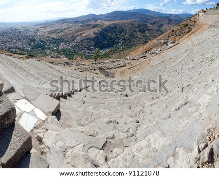 The Hellenistic Theater in Pergamon or Pergamum with a seating capacity of 10,000. Fisheye lens shot with a view to the city. Ruins of Temple of Dionysos in the distace and new city Bergama.