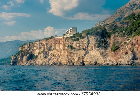 The high cliffs next to the central beach of Budva make the coastline even more scenic and romantic for boat trips, Montenegro. - stock photo