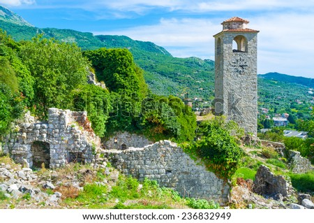 The high clock tower overlooks the ruins of the medieval fortress and green mountains, surrounding Stari Bar, Montenegro. - stock photo
