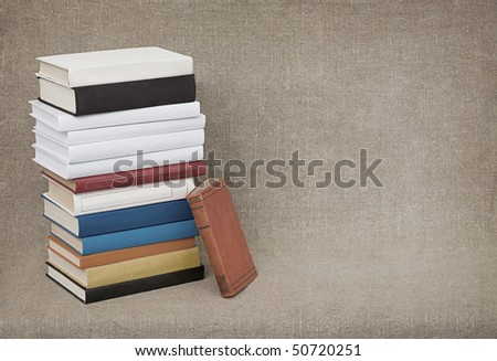 The high pile of old books and textbooks on the background of the canvas - stock photo