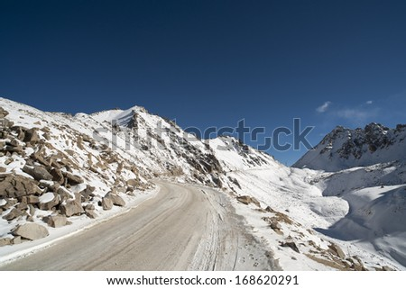 the highroad,snow mountain and blue sky with white cloud under the winter sunlight. - stock photo