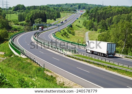 The highway between woods, in the middle of the highway electronic toll gates, moving trucks, in the distance Bridges - stock photo